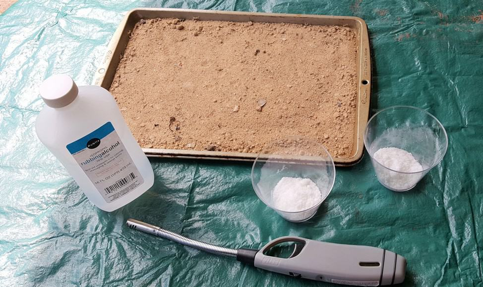 On a table with a green table cloth there is a cookie sheet filled with sand, a bottle of rubbing alcohol, 2 cups filled with sugar and a lighter