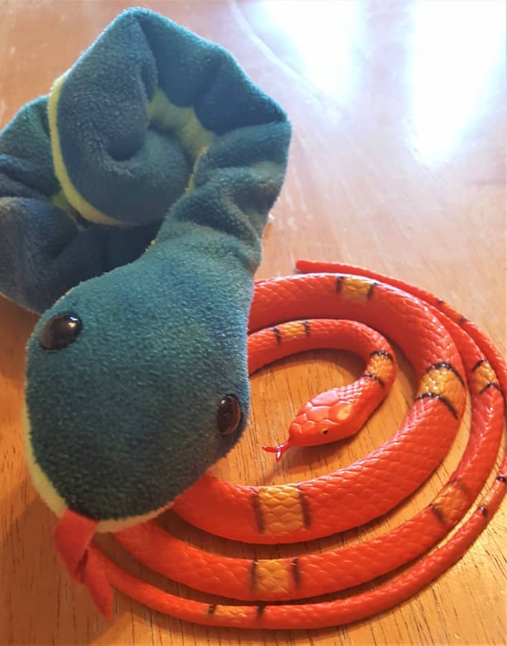 image of orange and yellow plastic snake and a stuffed green snake
