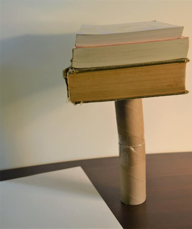 A table with a piece of white paper, a tube on its end with 3 books stacked on it