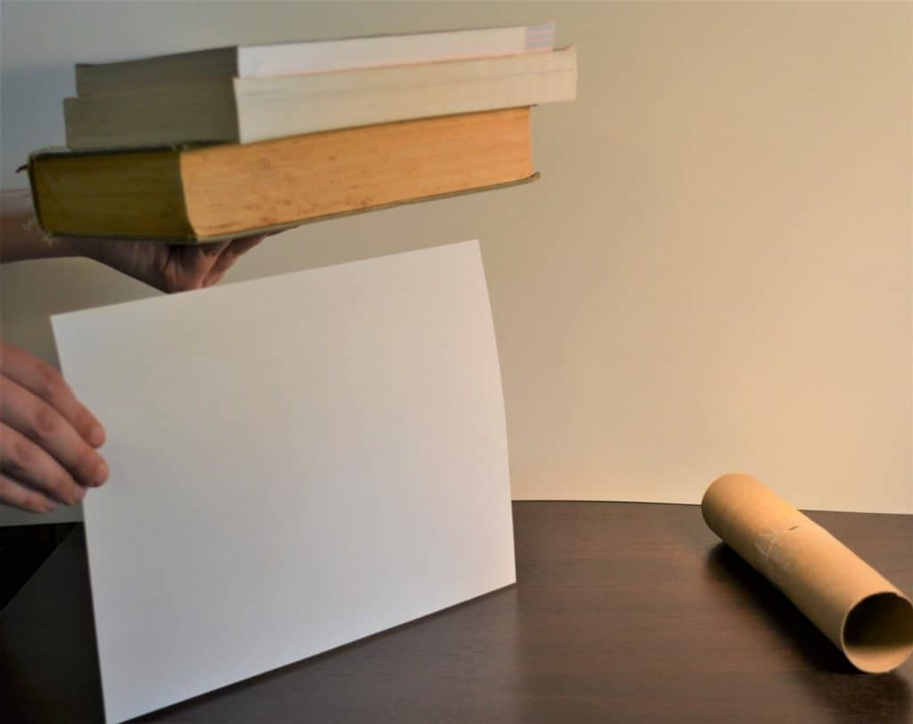 A table with a hand holding a piece of white paper on its landscape end attempting to stack the books on the edge of the paper. A tube is on its side on the table.
