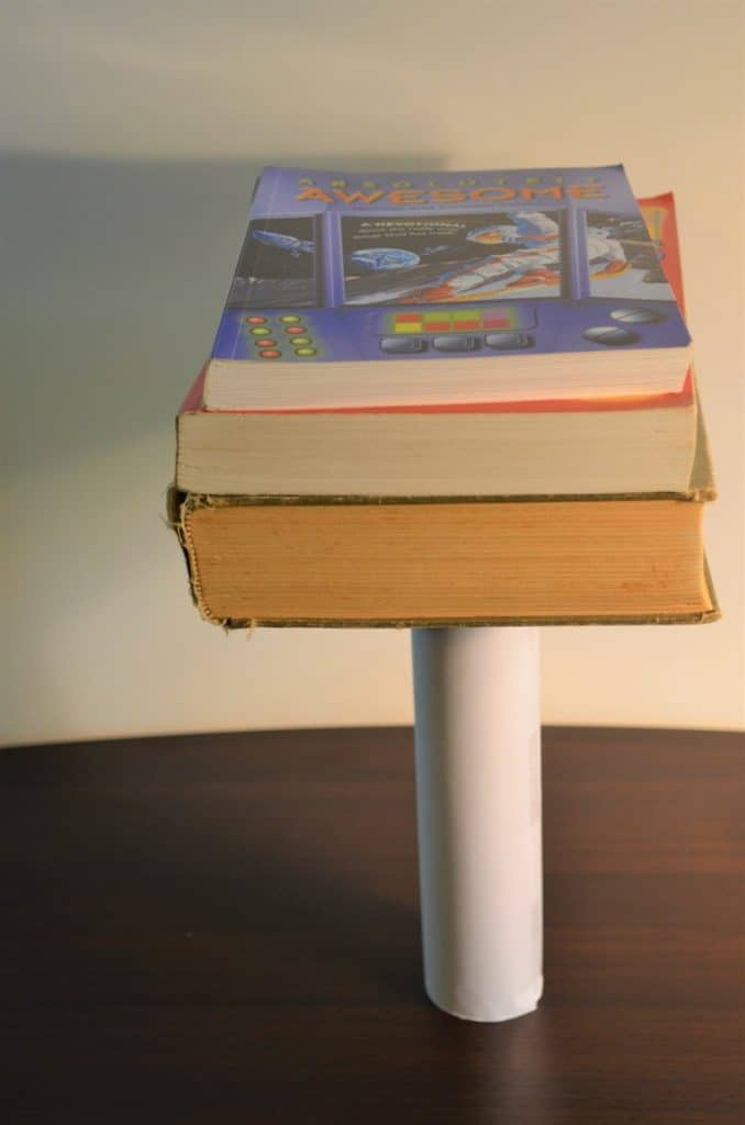Table with tube on end that now has the white paper around it with three books balanced on top of the tube.