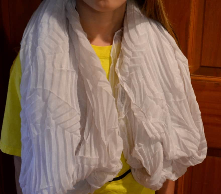 Child with white scarf wrapped around neck and shoulders
