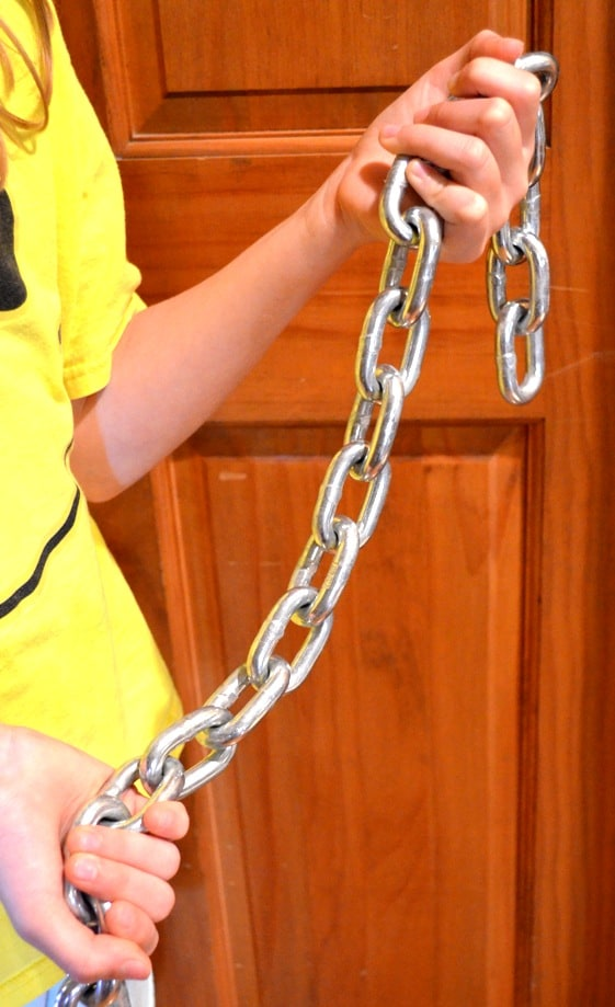 Child holding a heavy chain with both hands