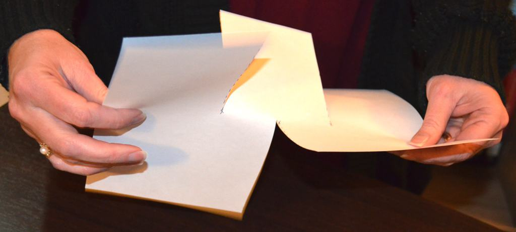 two hands twisting the cut sheet of paper
