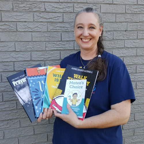image of FutureFlyingSaucers object lessons owner holding books in front of a brick wall